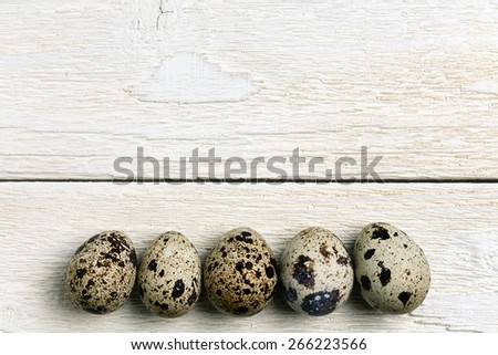 Row of the quail eggs on the wooden table. Top view. - stock photo