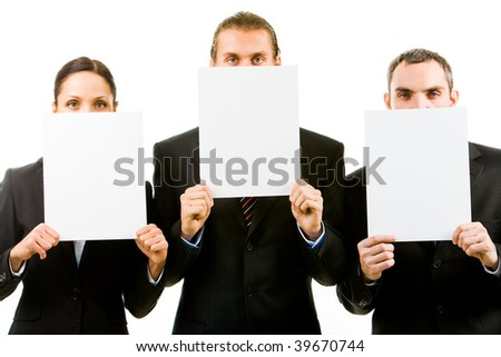 Row of three business partners holding blank papers by faces