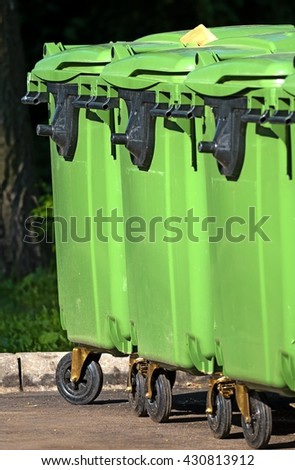 row of three green large plastic trash cans on wheels with black handles vertical crop close up - stock photo