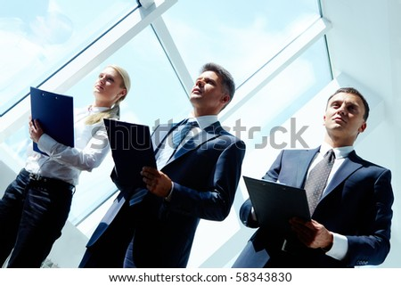 Row of three smart employees listening to report at conference