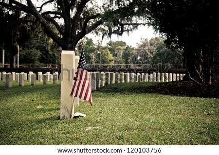 Row of tombstones at Beaufort National Cemetery in Beaufort South Carolina, with American Flag in ground of first gravesite - stock photo