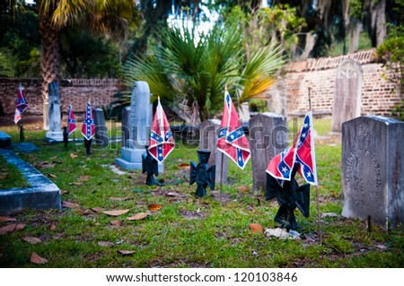 row of tombstones inside a cemetery, with confederate flags at the base of gravesites.  Flags denote burial is for a confederate soldier from the civil war - stock photo