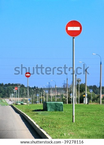 "Row of traffic signs ""No entry"" on the road side - stock photo"