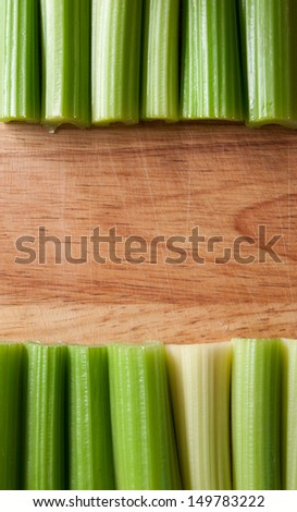 Row of trimmed green celery stalks against wooden chopping board background - stock photo