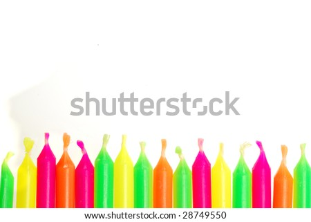 Row of unlit birthday candles isolated on white background