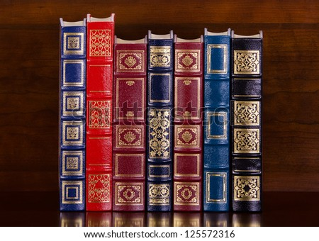 Row of vintage leather books on mahogany bookshelf - stock photo