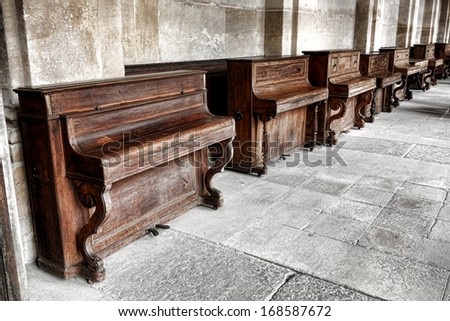 Row of vintage upright study pianos with weathered wood cabinet in an old music school lesson hall with antique stone walls and floors  - stock photo