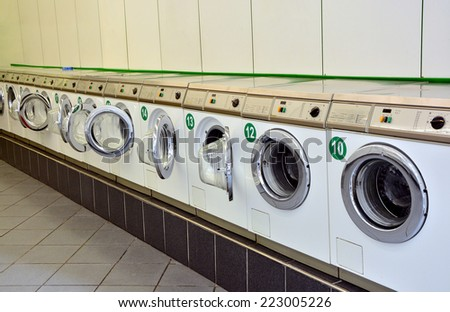 Row of washing machines in a public laundromat - stock photo