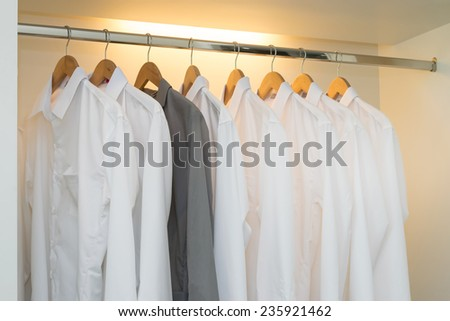 row of white and grey shirts hanging on coat hanger in white wardrobe  - stock photo
