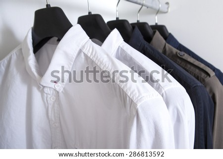row of white and grey shirts hanging on coat hanger in white wardrobe