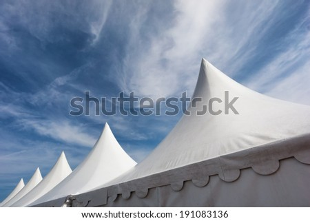 row of white event and party tents against blue sky - stock photo