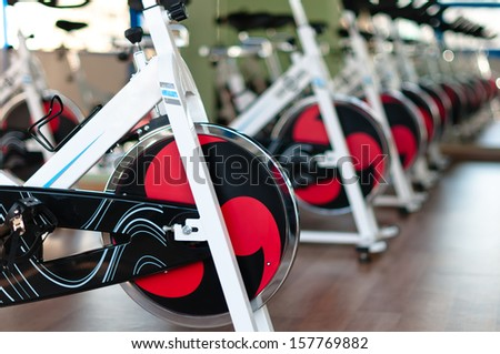 Row of white, metal bicycle trainers inside gym