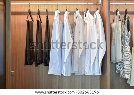 row of white shirts hanging in wooden wardrobe - stock photo