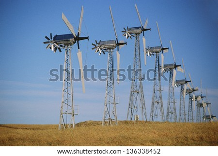 Row of wind turbines against blue sky (slight noise) - stock photo
