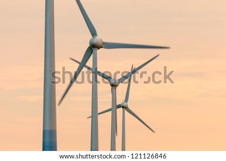 Row of wind turbines during an orange summer sunset - stock photo