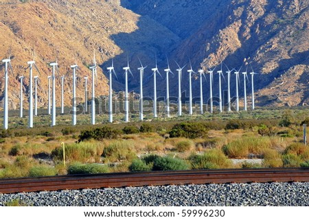 Row of windmills against the mountains. - stock photo