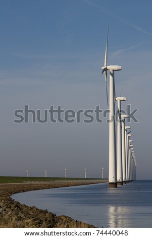 Row of windmills standing in the water - stock photo