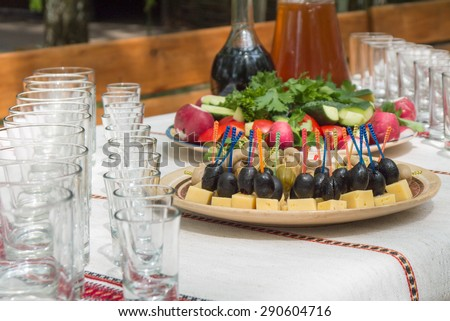 Row of wineglasses and plate with canapes - stock photo