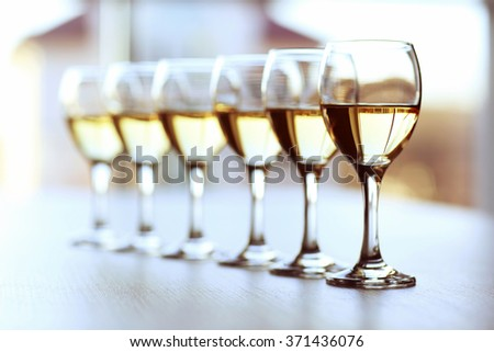 Row of wineglasses on light blurred background - stock photo