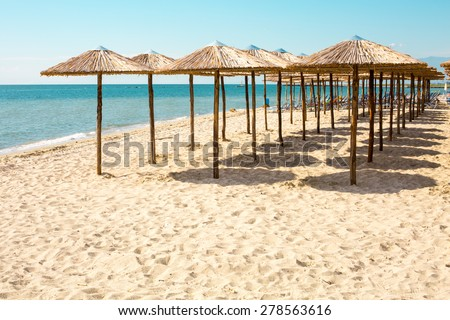 Row of wooden umbrellas at sandy beach, sea and blue sky background, Greece. Place for text - stock photo