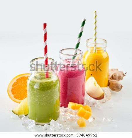 Row three jars of apple, mango and strawberry smoothie beverages surrounded by ice cubes and various pieces of fruit over gray background - stock photo