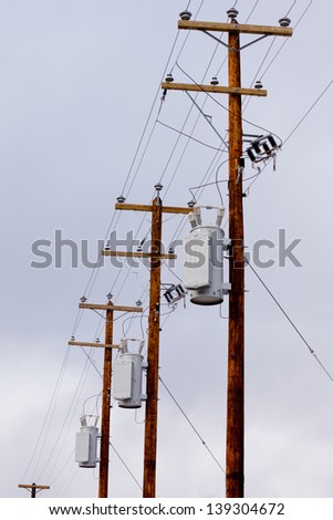 Row utility poles hung with electricity power cables and transformers for residential electric power supply - stock photo