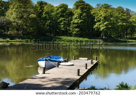 Rowboat on a peaceful pond in summer surrounded by woods - stock photo