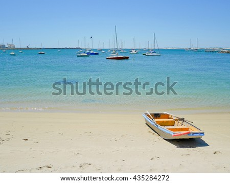 Rowboat on the beach with yachts background - stock photo