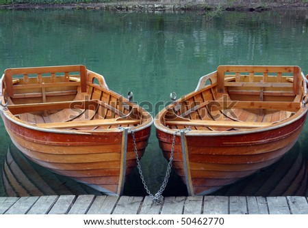 Rowboats parked in a row near a clear water lake - stock photo