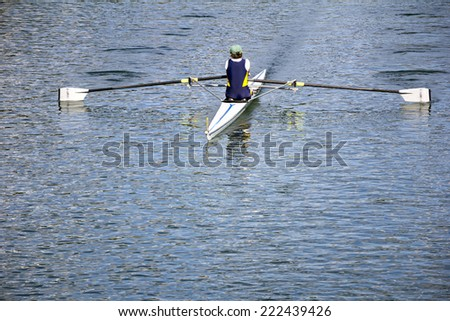 Rower in a boat, rowing on the tranquil lake - stock photo