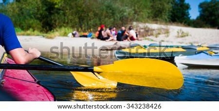 rowers on canoe floating to shore - stock photo