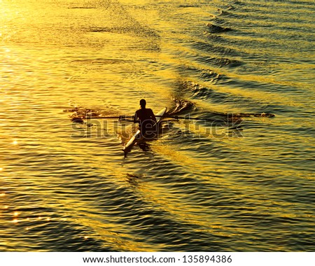 Rowing alone at sunset - stock photo