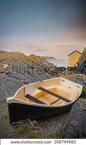 Rowing boat on coastal rocks next to a house near the sea - stock photo