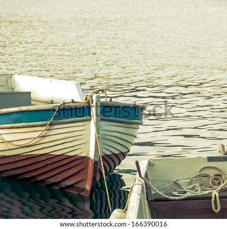 Rowing boats moored at sea port. Fishing boats with reflection on sea surface. Vintage motorboats mooring in harbor. - stock photo