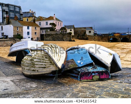 Rowing boats on slipway; small rowing boats resting on slipway against background of sandy beach, houses and ocean  - stock photo