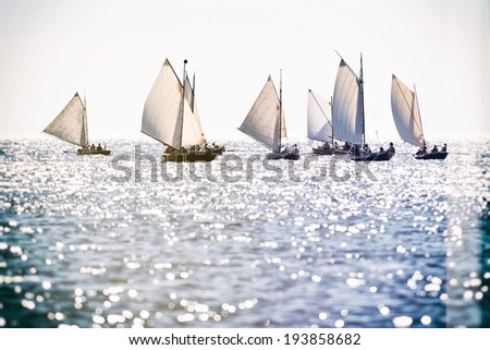 Rowing boats with sails in sunny weather with filter applied for a vintage look - stock photo