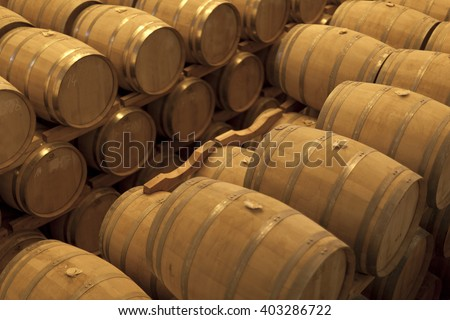 Rows of aging Whiskey barrels in a warehouse
