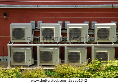 Rows of air conditioning units on a wall - stock photo