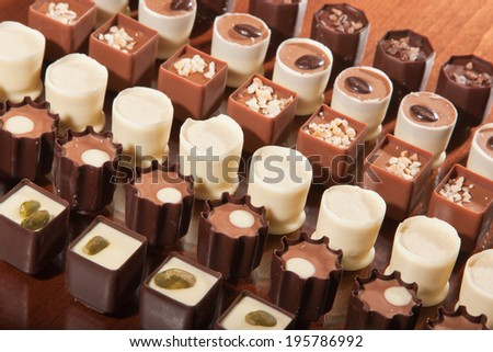 Rows of artisan chocolate truffles lined up by type on a wooden table. - stock photo