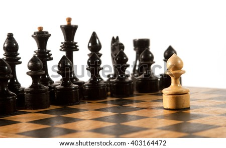 Rows of black chess figures and a single white pawn on the chessboard (isolated on white, selective focus on the white pawn) - stock photo