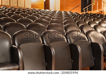 rows of black cozy chairs in a small theater - stock photo