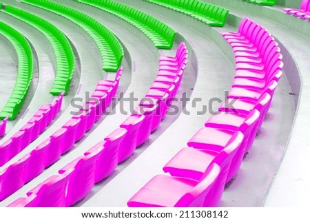 rows of brightly colored empty stadium seats - stock photo