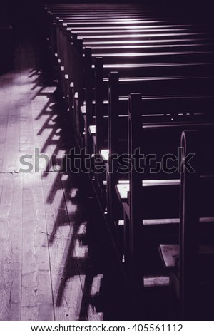 Rows of church benches. Sunlight filtered through the stained glass window. Selective focus. Toned monochrome photo. - stock photo