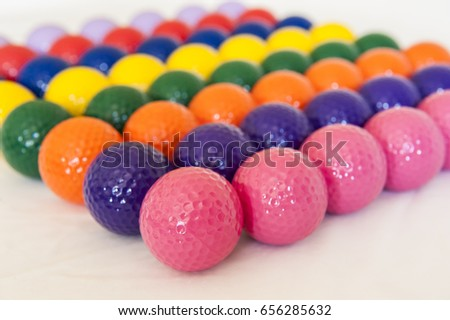 Rows of colorful mini golf balls on white background