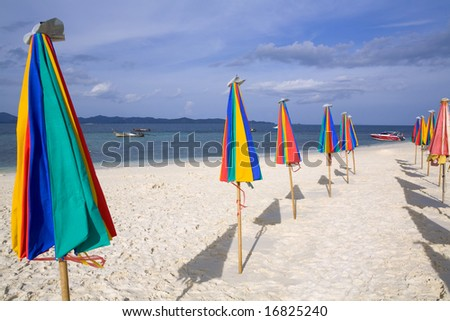 Rows of colorful umbrellas on the beach - stock photo
