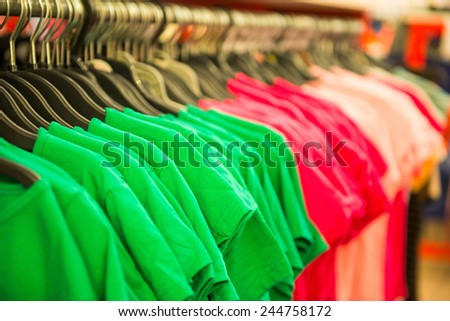 rows of cotton T-shirts in a large store - stock photo