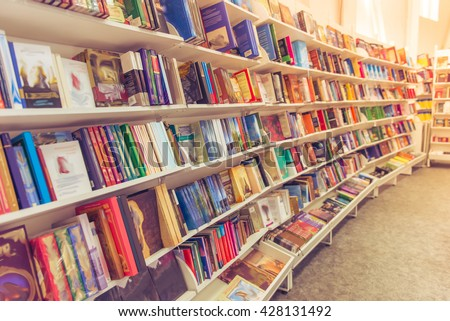 Rows of different colorful books lying on the shelves in the modern urban bookshop
