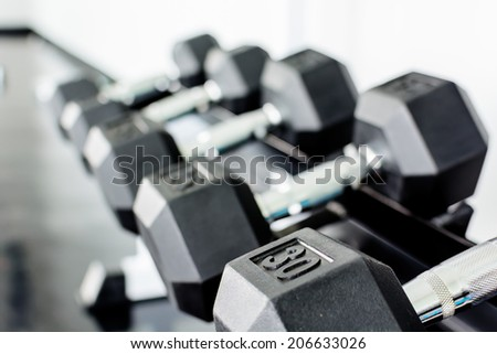 rows of dumbbells on a rack in a gym - stock photo