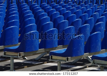 Rows of empty blue plastic chairs - stock photo