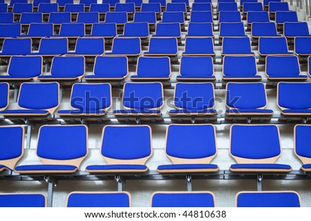 Rows of empty blue stadium seats background